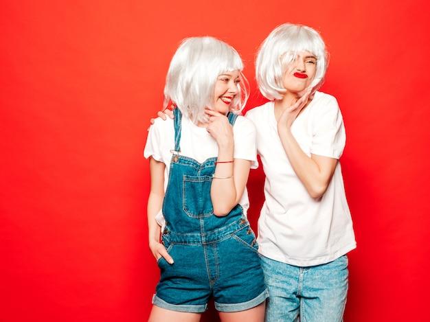 Deux jeunes filles sexy hipster souriant en perruques blanches et lèvres rouges. belles femmes à la mode dans des vêtements d'été. modèles sans soucis posant près du mur rouge en studio l'été devient fou