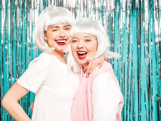 Deux jeunes filles sexy hipster souriant en perruques blanches et lèvres rouges.belles femmes à la mode en été vêtements d'été
