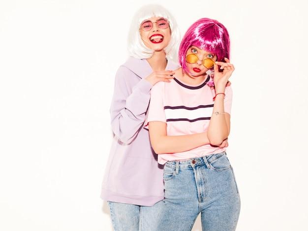 Deux jeunes filles sexy hipster souriant en perruques et lèvres rouges. belles femmes à la mode dans les vêtements d'été. modèles sans soucis posant près du mur blanc en studio devenant fou et étreignant