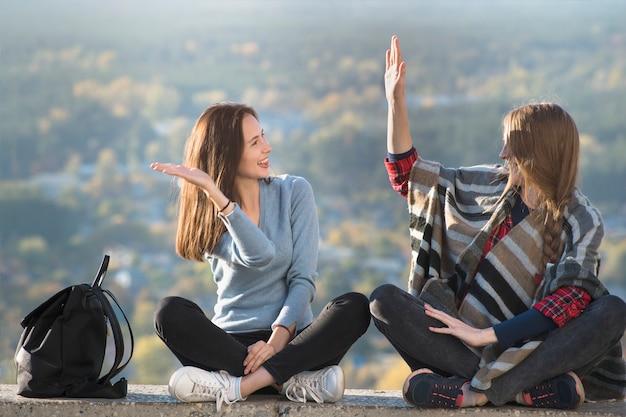 Deux jeunes filles souriantes s'amuser assis sur une colline