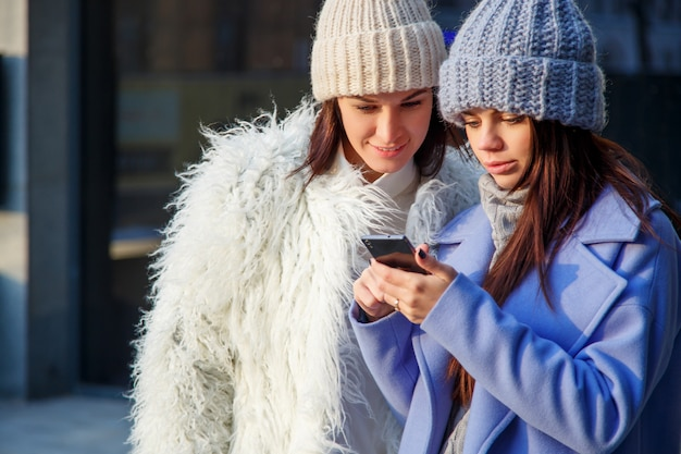 Deux jeunes filles utilisent un téléphone ensemble à l'extérieur