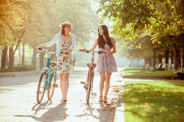 Les deux jeunes filles avec des vélos dans le parc