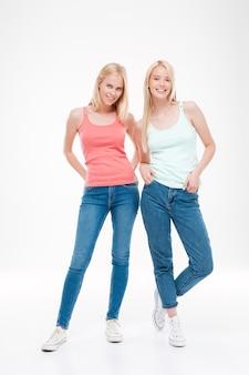 Deux jeunes filles vêtues de t-shirts et de jeans posant. isolé sur un mur blanc. regardant devant.