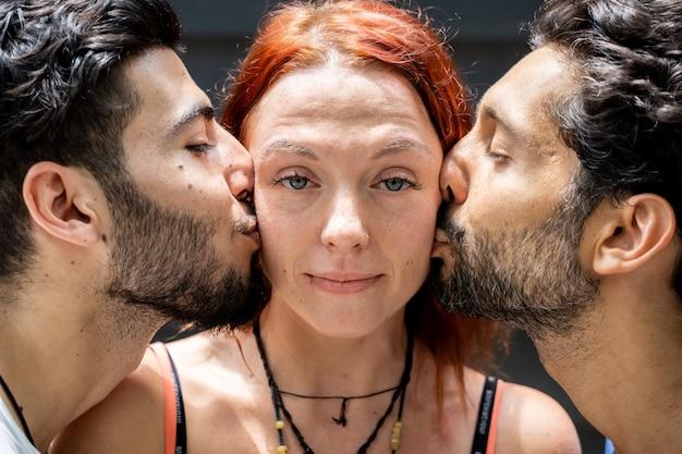 Deux jeunes garçons d'ethnies différentes s'embrassant sur la joue d'une fille debout au milieu