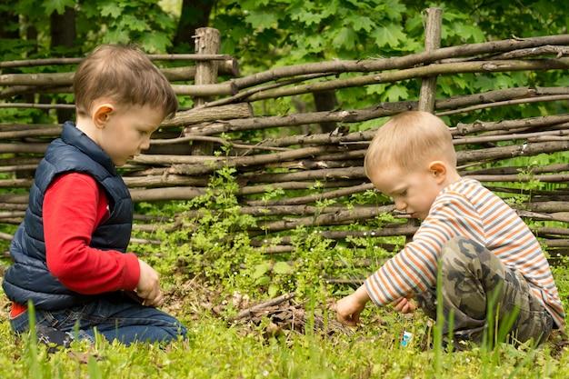 Deux jeunes garçons jouant à allumer un feu de camp