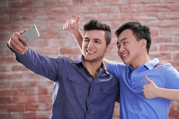 Deux jeunes garçons prenant selfie avec téléphone mobile sur l'espace de mur de brique