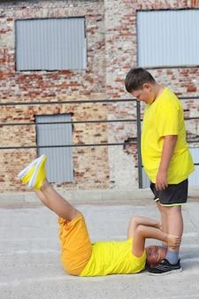 Deux jeunes garçons vêtus de tee-shirts jaunes s'entraînent. entraînement des muscles abdominaux. photo de haute qualité