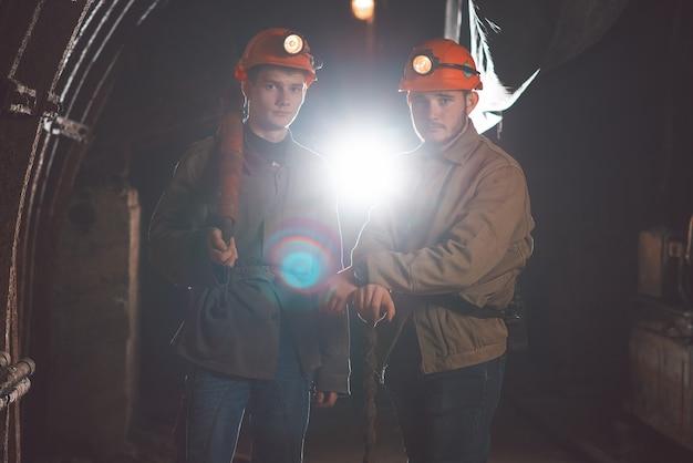 Deux jeunes gars portant des vêtements spéciaux et des casques debout dans la mine