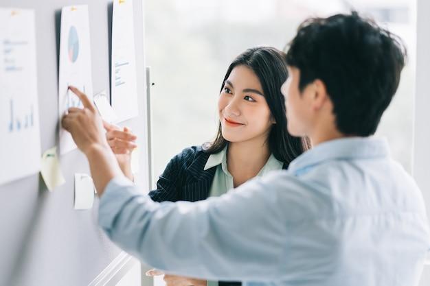 Deux jeunes gens d'affaires asiatiques discutent des plans à venir