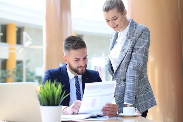 Deux jeunes gens d'affaires utilisant un ordinateur portable au bureau tout en collaborant à un projet de démarrage.