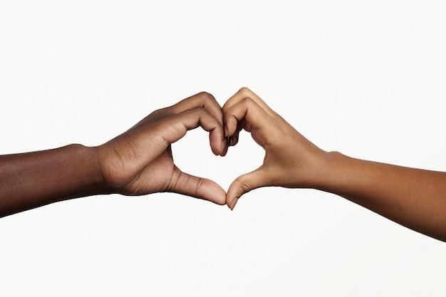 Deux jeunes gens à la peau sombre se tenant la main en forme de coeur, symbolisant l'amour, la paix et l'unité.