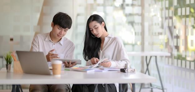 Deux jeunes graphistes professionnels travaillant ensemble sur leur projet dans un bureau moderne