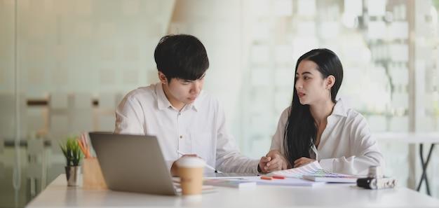Deux jeunes graphistes professionnels travaillant sur leur projet avec un ordinateur portable dans un bureau moderne