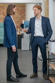 Deux jeunes hommes adultes souriants en costumes sombres communiquant dans un espace de bureau de bonne humeur