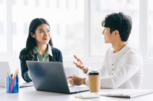 Deux jeunes hommes d'affaires asiatiques discutent du projet de fin d'année