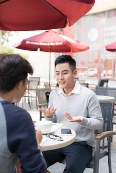 Deux jeunes hommes d'affaires beaux dans des vêtements décontractés souriant, parlant, buvant du café tout en travaillant au bureau
