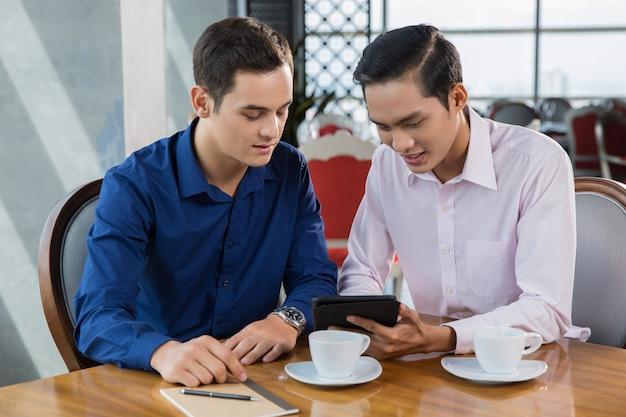 Deux jeunes hommes d'affaires discuter du projet sur tablet