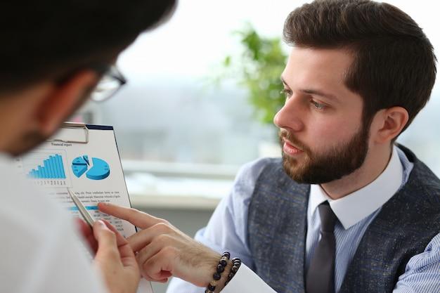 Deux jeunes hommes d'affaires travaillant avec graphique financier