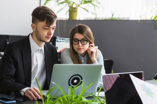 Deux jeunes hommes d'affaires utilisant un ordinateur portable sur le lieu de travail