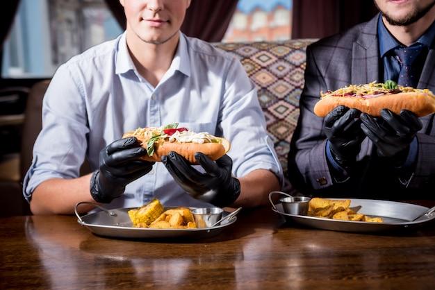 Deux jeunes hommes affamés mangeant un hot-dogs au café. restaurant