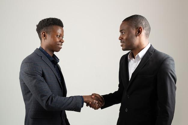Deux jeunes hommes africains en costumes se serrant la main