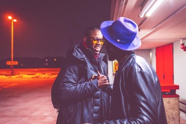 Deux jeunes hommes africains à l'extérieur salutations