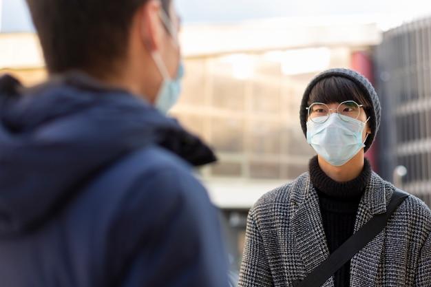 Deux jeunes hommes asiatiques dans des masques de protection médicale contre covid-2019 parler