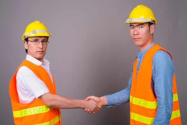 Deux jeunes hommes asiatiques ouvrier du bâtiment ensemble contre mur gris