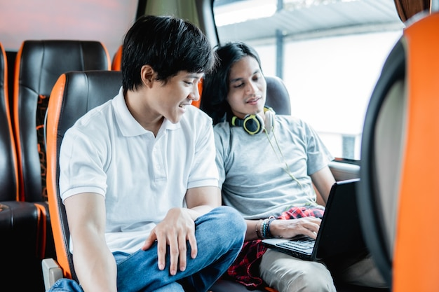 Deux jeunes hommes assis sur un ordinateur portable ensemble dans le bus lors d'un voyage