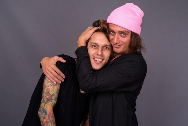 Deux jeunes hommes beaux ensemble contre un mur gris