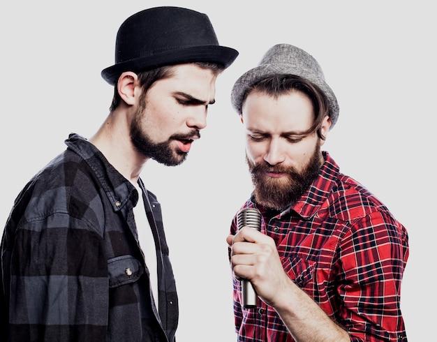 Deux jeunes hommes chantant avec microphone