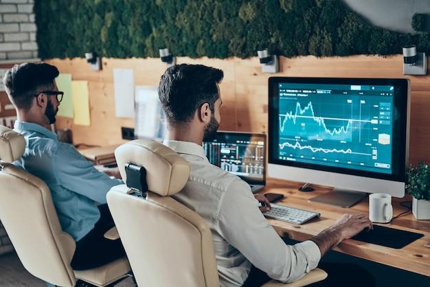 Deux jeunes hommes concentrés en tenues de soirée travaillant à l'aide d'ordinateurs assis au bureau