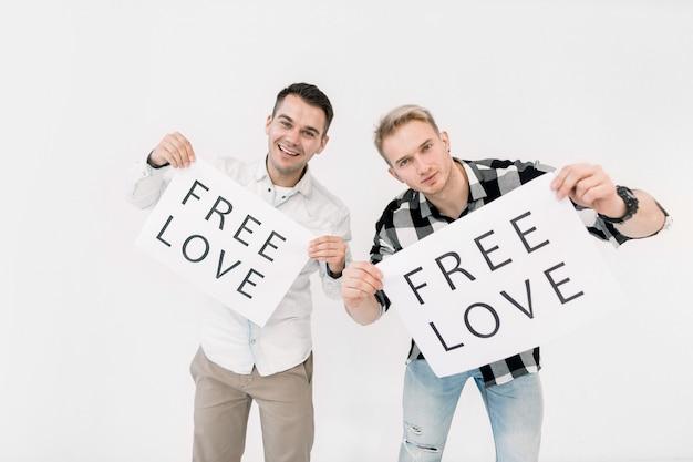 Deux jeunes hommes, couple gay, tenant des affiches en papier avec texte free love, pour les droits des lgbt, l'égalité des sexes