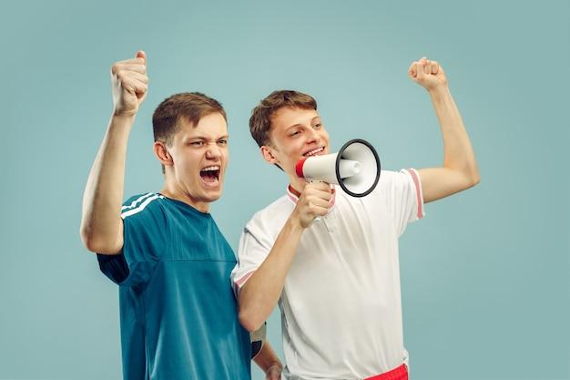 Deux jeunes hommes debout dans des vêtements de sport isolés sur bleu