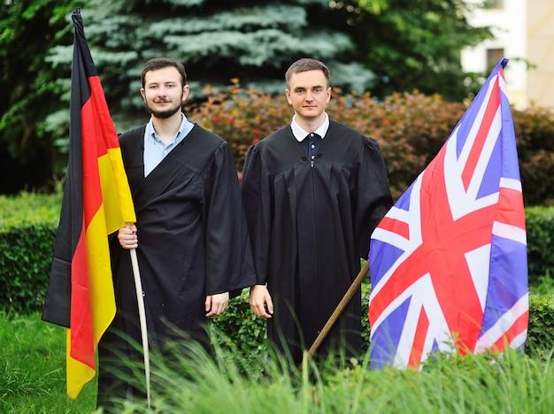 Deux jeunes hommes étudiants diplômés de la faculté des langues étrangères en robe tiennent les drapeaux de l'allemagne et de la grande-bretagne dans leurs mains