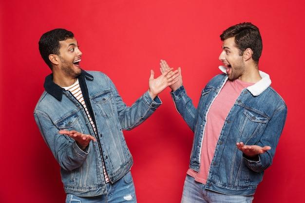 Deux jeunes hommes excités amis portant des vestes en jean debout isolé sur mur rouge, célébrant
