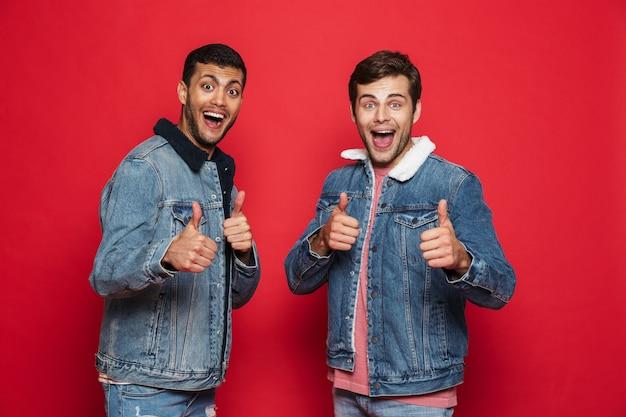 Deux jeunes hommes excités amis portant des vestes en jean debout isolé sur mur rouge, donnant les pouces vers le haut
