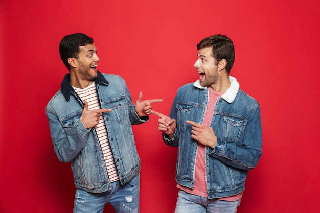 Deux jeunes hommes excités amis portant des vestes en jean debout isolé sur mur rouge, pointant les uns vers les autres