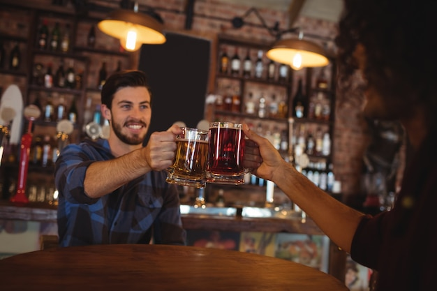 Deux jeunes hommes grillant leurs chopes à bière