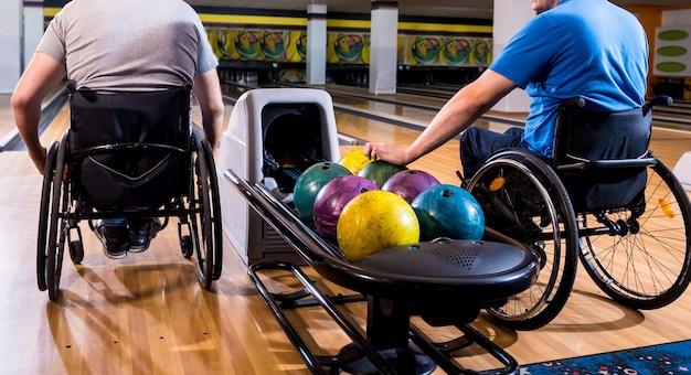 Deux jeunes hommes handicapés en fauteuil roulant jouant au bowling dans le club