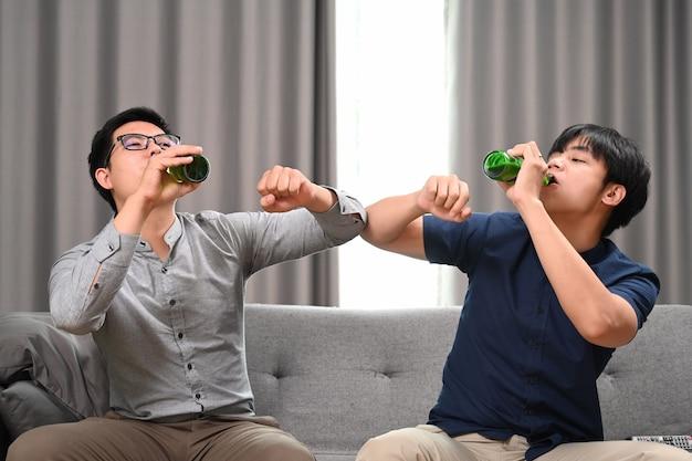 Deux jeunes hommes heureux buvant de la bière et célébrant la victoire à la maison.