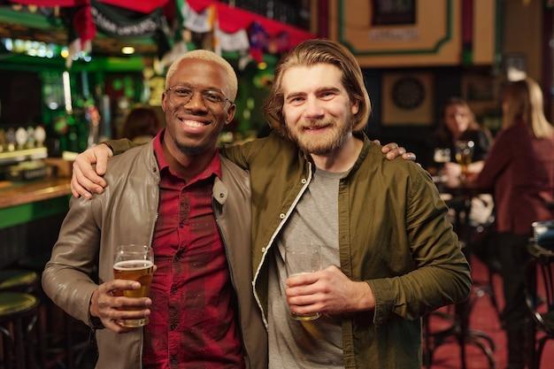 Deux jeunes hommes interculturels joyeux vous regardent tout en grillant avec des verres de bière devant la caméra contre des invités assis à table dans un pub