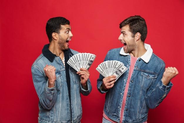 Deux jeunes hommes joyeux debout isolé sur mur rouge, tenant des billets d'argent, célébrant
