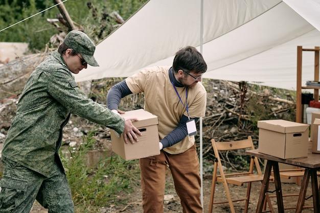 Deux jeunes hommes livrant des boîtes avec un don