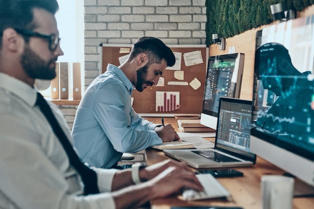 Deux jeunes hommes modernes concentrés en tenues de soirée travaillant à l'aide d'ordinateurs assis au bureau