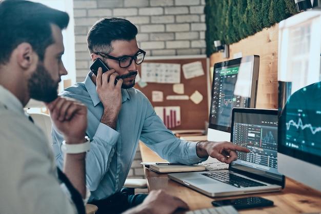 Deux jeunes hommes modernes et confiants en tenues de soirée travaillant à l'aide d'ordinateurs assis au bureau