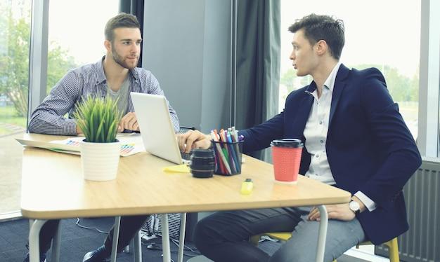 Deux jeunes hommes modernes discutant du travail au bureau.