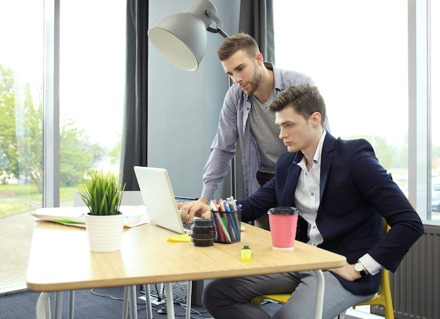 Deux jeunes hommes modernes discutant du travail dans le studio de bureau.