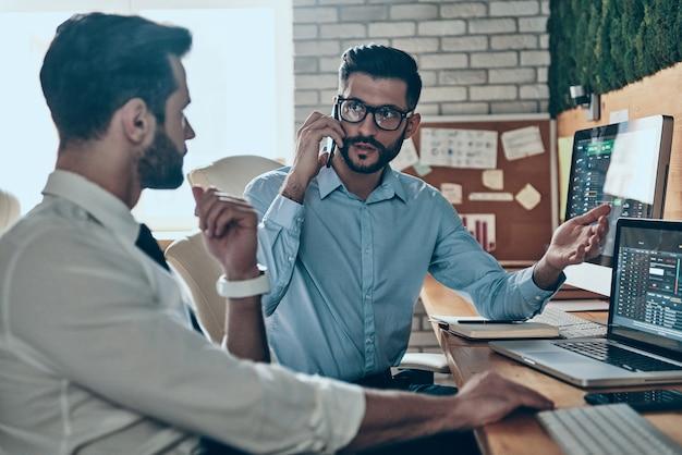 Deux jeunes hommes modernes occupés en tenues de soirée travaillant à l'aide d'ordinateurs tout en étant assis au bureau