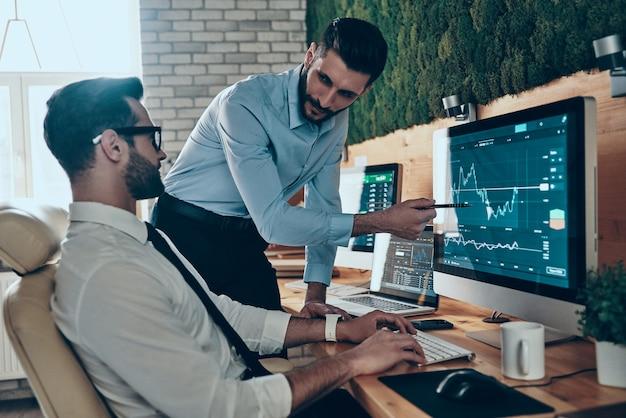 Deux jeunes hommes modernes en tenue de soirée travaillant à l'aide d'ordinateurs assis au bureau